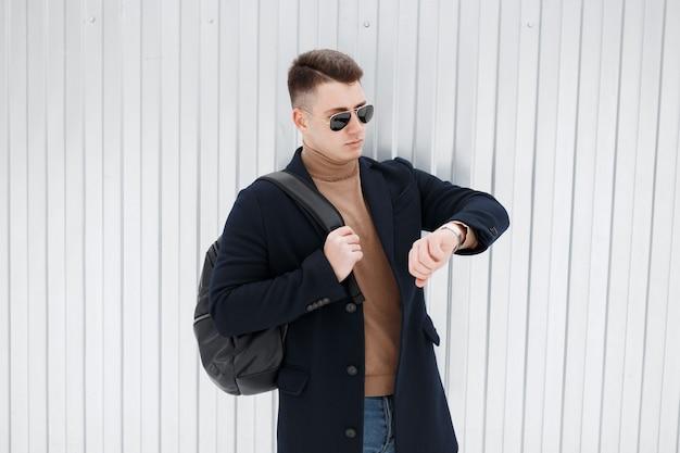 금속 벽 근처 야외에서 배낭 니트 빈티지 스웨터에 청바지에 고전적인 검은 코트에 세련된 선글라스에 젊은 힙 스터 남자가 손에 보이는