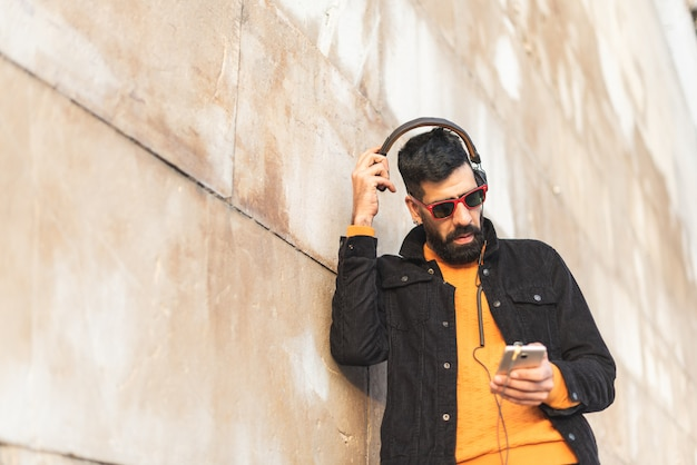 Young hipster man listening music on headphones.