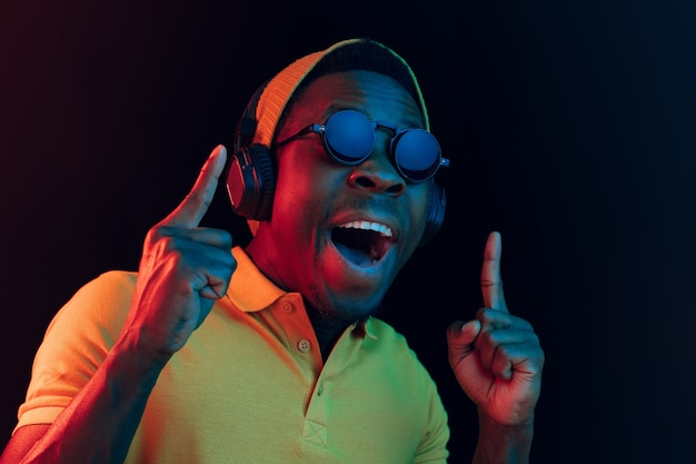 ネオンライト付きの黒いスタジオでヘッドフォンで音楽を聴いている若い流行に敏感な男。