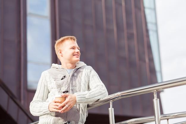 Битник молодой человек на улице, пить кофе в солнечный день