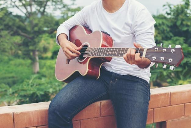 Il giovane hipster, a suonare la chitarra di relax sulla sua vacanza, enj