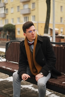 Young hipster man sits on a bench, looks away, in winter outside