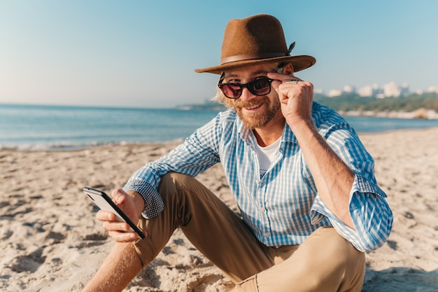 Young hipster man sitting on beach by sea on summer vacation, boho style outfit, holding using internet on smartphone