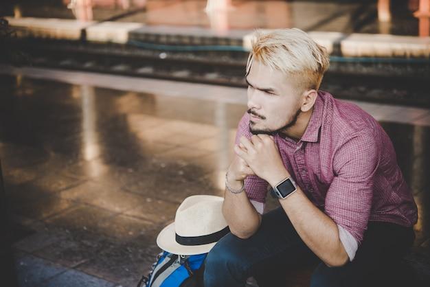 Giovane uomo hipster seduto sulla panca di legno con zaino alla stazione ferroviaria. uomo seduto in attesa del treno alla piattaforma.