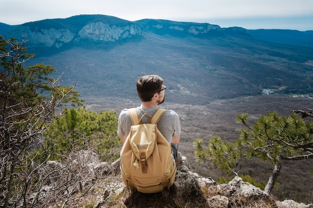 Young hipster man in the spring mountains. hipster with a backpack behind his back goes on a trip