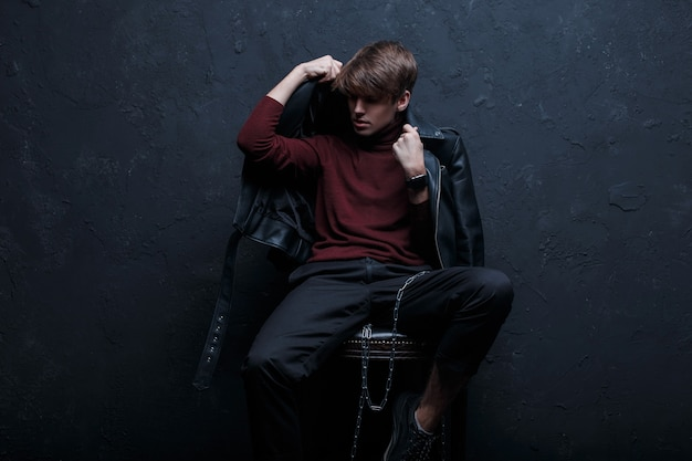 Young hipster man in stylish vintage jacket in red golf in stylish jeans in black sneakers with a metal chain sits and poses on a chair in a studio near the wall. attractive trendy modern guy