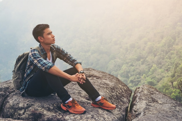 Young hipster man take a rest in the mountain top. travel lifestyle concept.