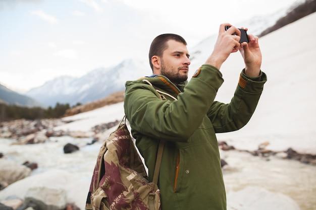 젊은 힙 스터 남자, 스마트 폰을 사용하여 사진 촬영, 야생의 자연, 겨울 방학, 하이킹