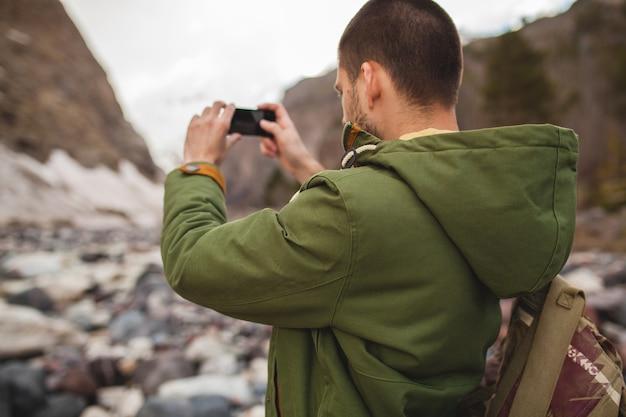 流行に敏感な若い男性、スマートフォン、野生の自然、冬休み、ハイキングを使用して写真を撮る