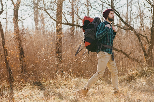 Young hipster man traveling with backpack in autumn forest wearing checkered shirt and hat, active tourist walking, exploring nature in cold season