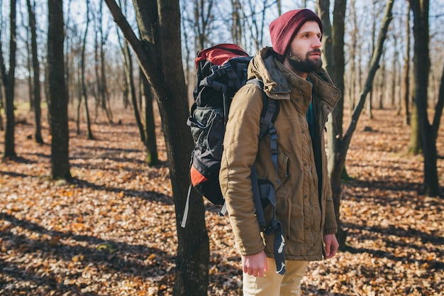 Young hipster man traveling with backpack in autumn forest wearing warm jacket and hat, active tourist, exploring nature in cold season