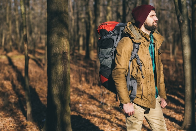 Uomo giovane hipster che viaggia con lo zaino nella foresta di autunno che indossa giacca calda e cappello, turista attivo, esplorando la natura nella stagione fredda