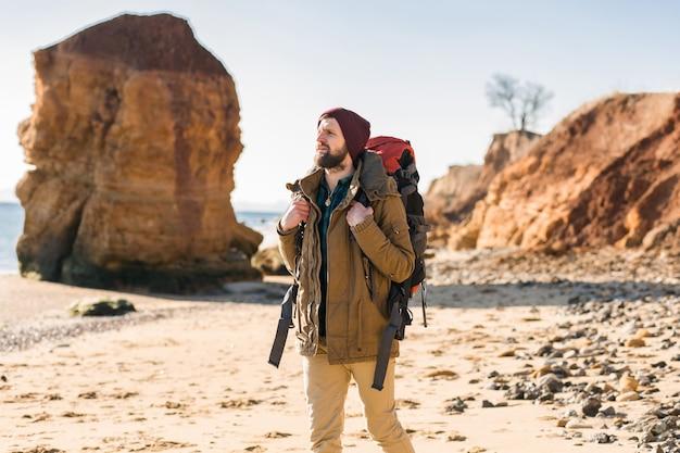 Giovane hipster che viaggia con lo zaino nella costa del mare autunnale indossando una giacca e un cappello caldi