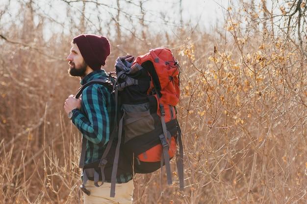 Молодой хипстерский мужчина путешествует с рюкзаком в осеннем лесу в клетчатой рубашке и шляпе, активный турист, исследующий природу в холодное время года