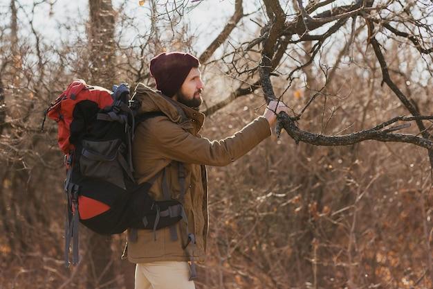 暖かいジャケットと帽子を身に着けている秋の森でバックパックを持って旅行する若い流行に敏感な男