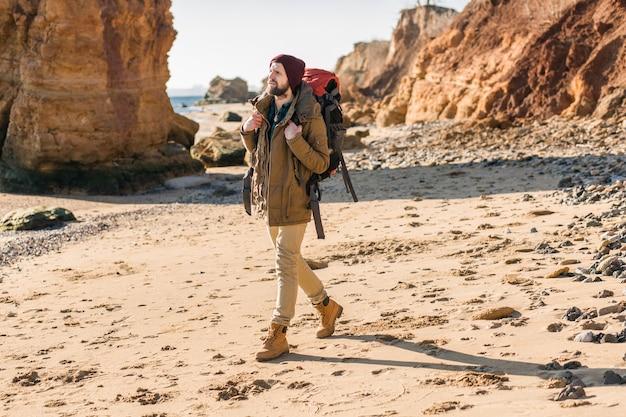 暖かいジャケットと帽子を身に着けている秋の海岸でバックパックを持って旅行する若い流行に敏感な男