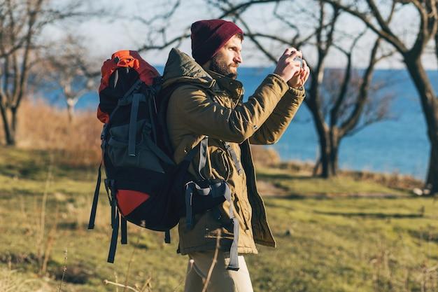 Uomo giovane hipster che viaggia con zaino indossando giacca calda e cappello, turista attivo, scattare foto sul cellulare, esplorare la natura nella stagione fredda