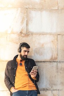 Young hipster man using cell phone and listening music .