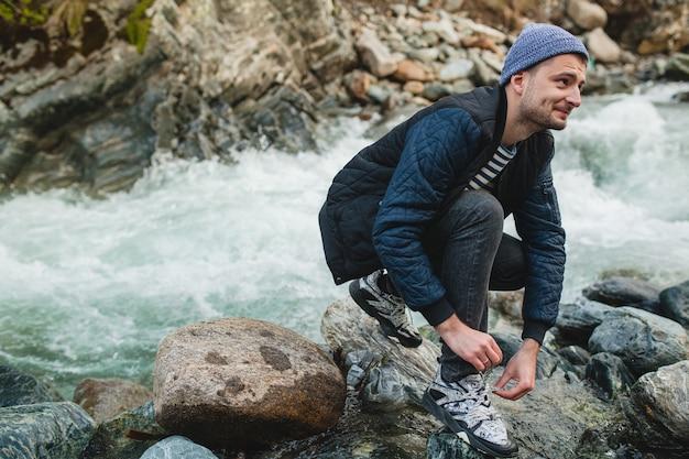 靴ひもを結ぶ冬の森の川の岩の上を歩く若い流行に敏感な男
