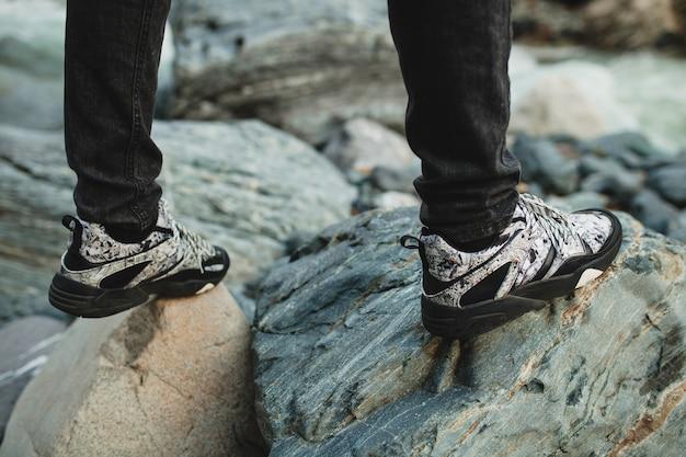 Битник молодой человек, идущий на скале у реки в зимнем лесу