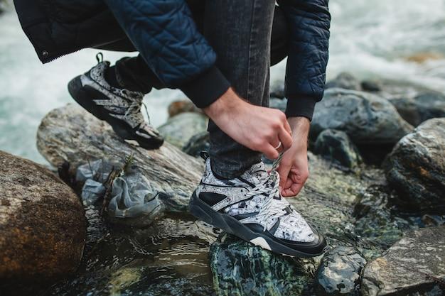 冬の森の川の岩の上を歩く流行に敏感な若い男