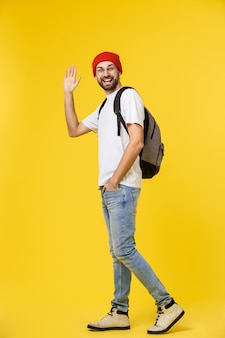 Young hipster man wearing hat , suspenders, isolate on yellow.