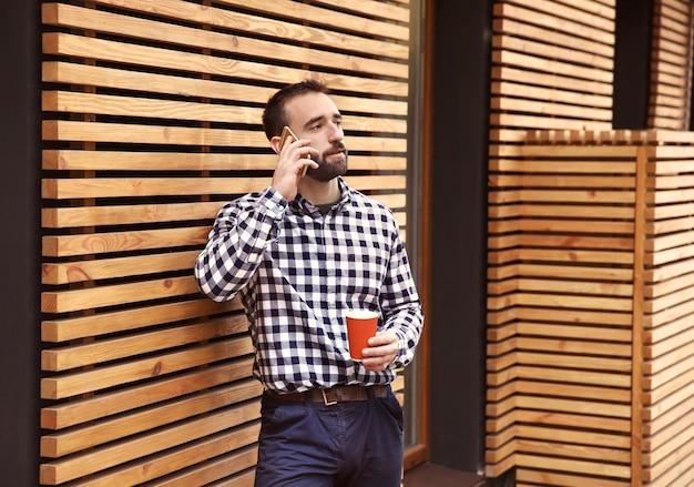 Битник молодой человек с кофе разговаривает по телефону на открытом воздухе