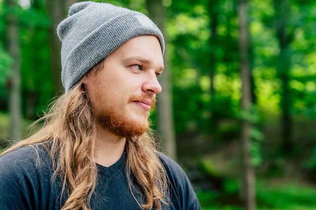 숲에서 긴 머리를 가진 젊은 hipster 남자