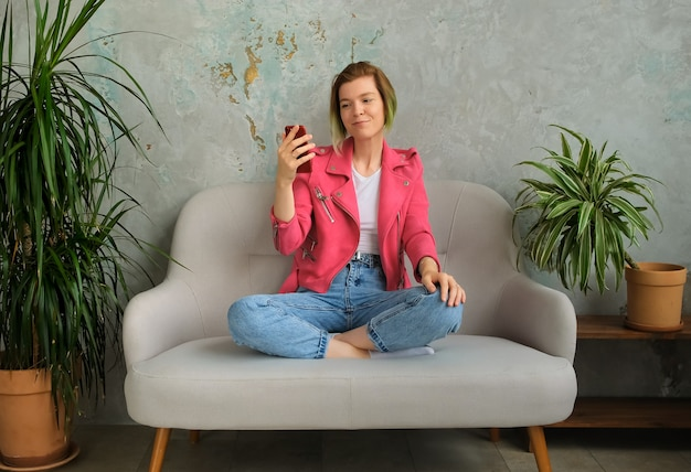 Young hipster millenial woman makes a video call and using a mobile phone.