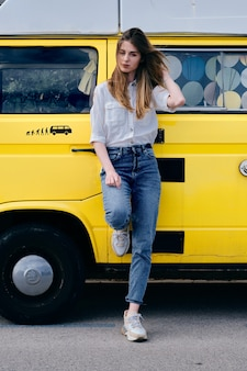 A young hipster model in front of her vintage van