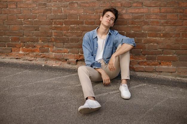 젊은 힙스터는 벽돌 벽 배경에 라벨이 없는 흰색 면 티셔츠를 보여주는 파란색 데님 버튼 업 셔츠에 앉아 있습니다.
