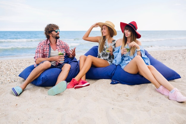 Giovane hipster sorridente compagnia di amici felici in vacanza seduti in sacchi di fagioli su una festa in spiaggia, bevendo cocktail mojito
