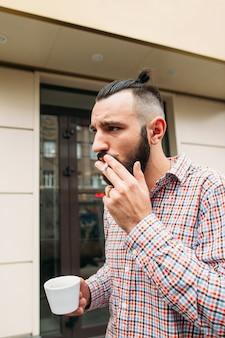 屋外で一杯のコーヒーと喫煙若いヒップスター