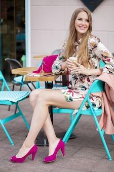 流行に敏感な若いスタイリッシュな女性のカフェ、春夏のファッショントレンドに座っています。