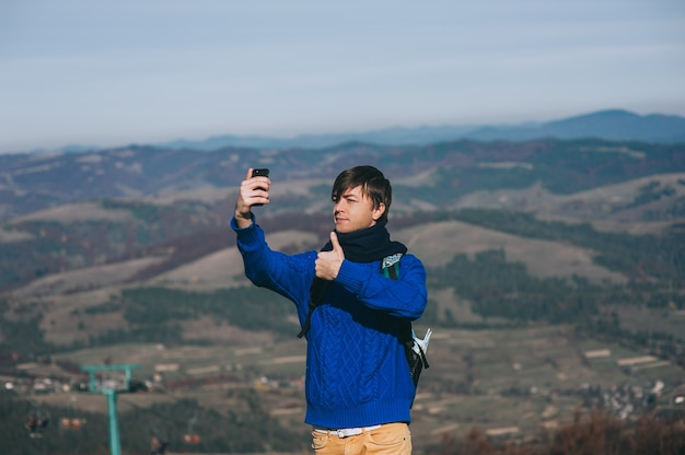 Young hipster taking photo by smart-phone on the peak of mountain