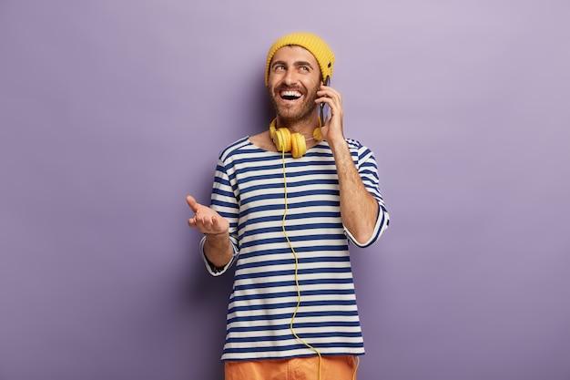 Il giovane hipster parla casualmente con un amico tramite smartphone, discute di qualcosa di divertente accaduto con lui, ha un'espressione felice del viso, indossa abiti eleganti, ascolta musica in cuffia. comunicazione