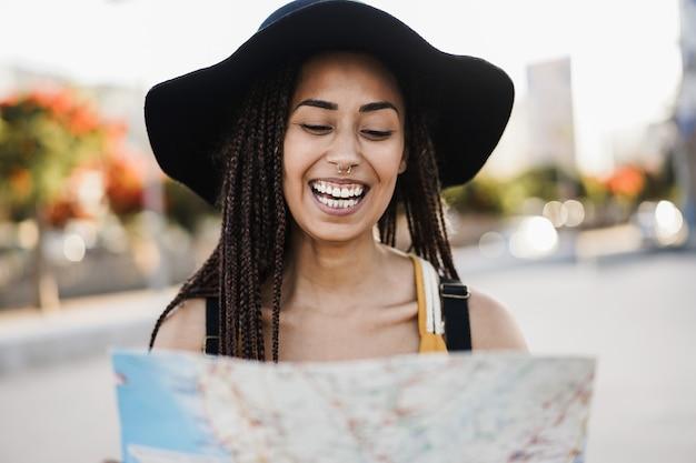 旅行の夏休み中に屋外の地図を使用して若い流行に敏感な観光客の女の子-顔に焦点を当てる Premium写真