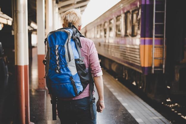 鉄道駅にバックパックと若いhipster観光。ホリデー観光コンセプト。