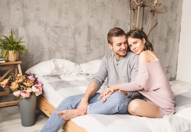 Young hipster with beard and attractive woman resting at home while sitting on bed at home