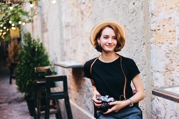 手でレトロなカメラで若い流行に敏感な椅子に座っているし、屋外の笑顔