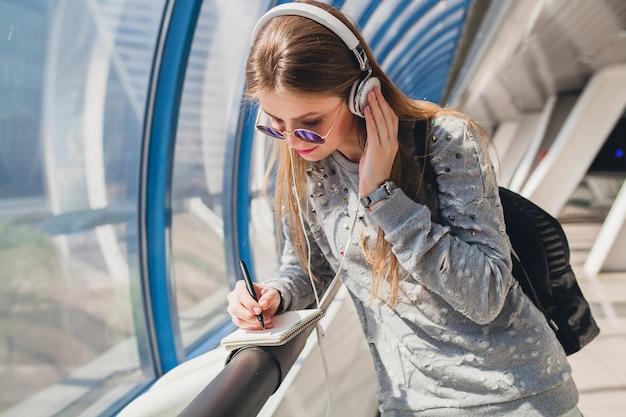 Giovane donna hipster in abito casual divertirsi ascoltando musica in cuffia, indossando maglione e occhiali da sole, studente che prende appunti