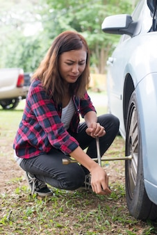 Young hipster woman checking out a flat tyre on her car try to fix.