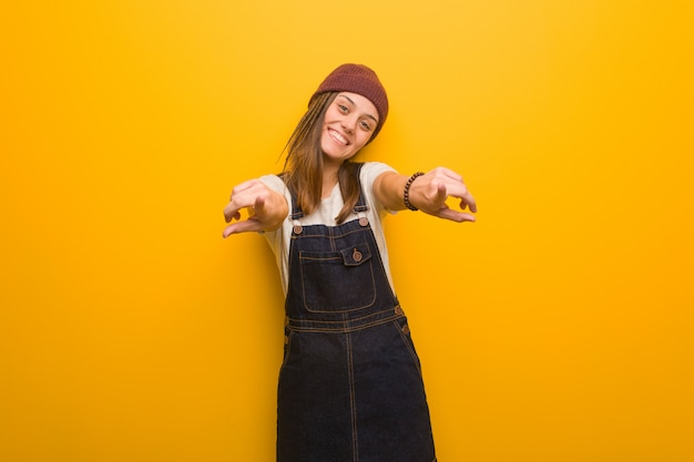 Young hipster woman cheerful and smiling pointing to front