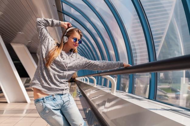 ヘッドフォンで音楽を聴いてカジュアルな服を着て都会のモダンな建物で楽しんで踊る若い流行に敏感な女性