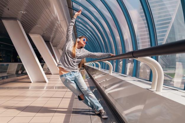 Donna giovane hipster che balla divertendosi in un edificio moderno urbano vestito in abito casual ascoltando musica in cuffia