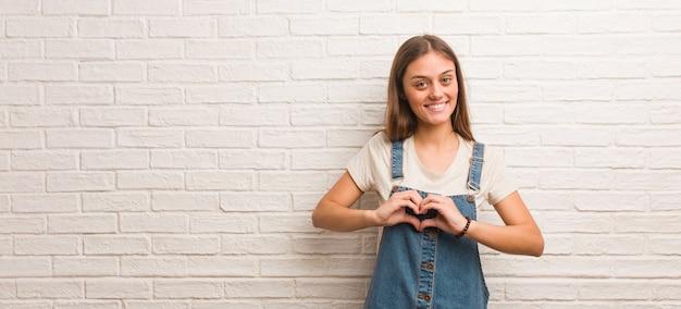 Битник молодая женщина делает форму сердца руками