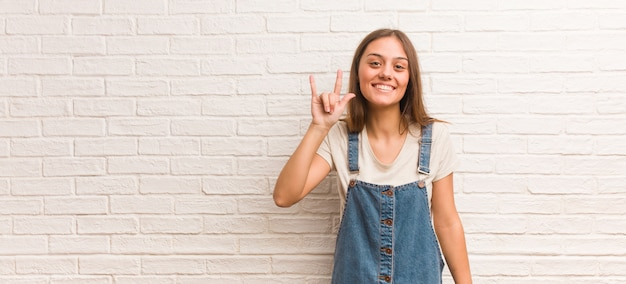 Young hipster woman doing a rock gesture