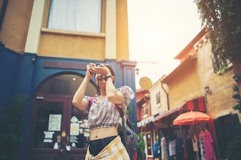 Young hipster woman enjoy taking photo in urban while traveling.