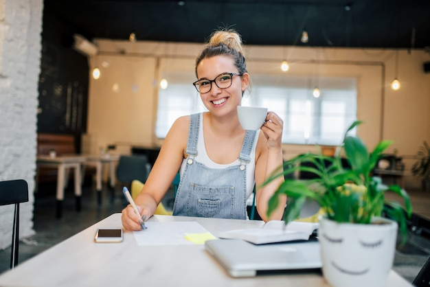 Young hipster woman in glasses studying and drinking coffee in a cafe.