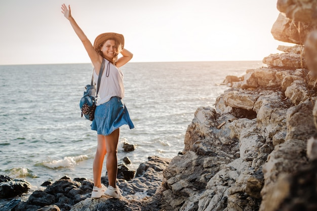 A young hipster woman in a hat and a rukzak with her hands up, standing on top of a cliff and looking at the sea at sunset.